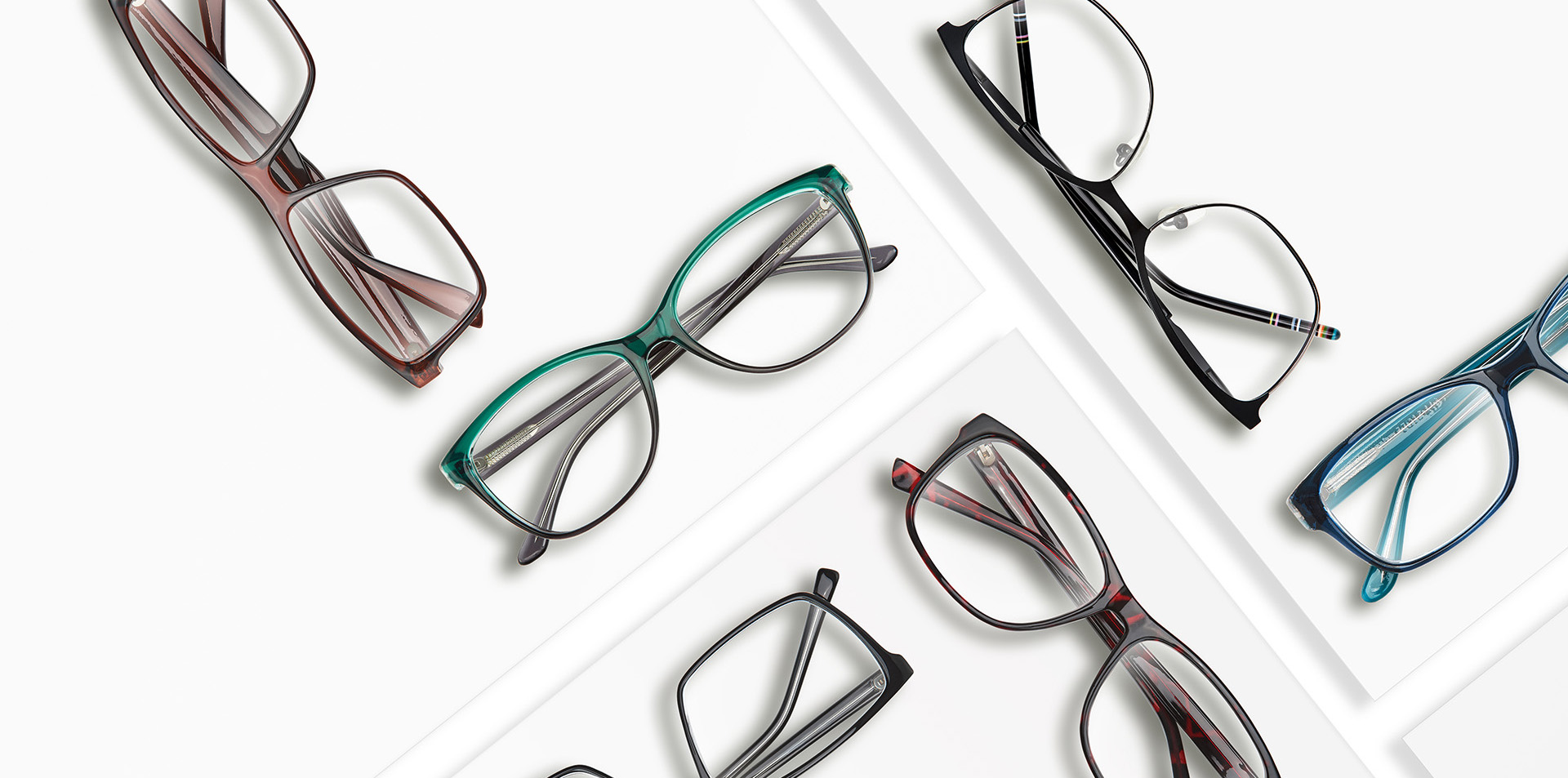 Composition of many different classic style glasses on white square stands. Studio photo.